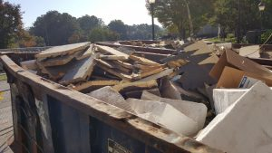 dumpster filled with roofing materials